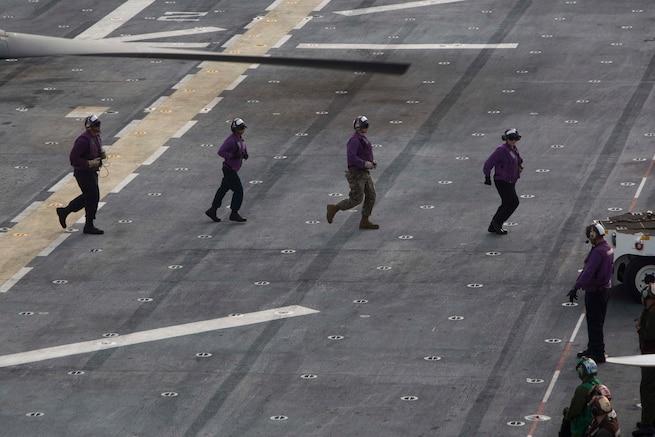 Sailors clear the flight deck on the USS Kearsarge.