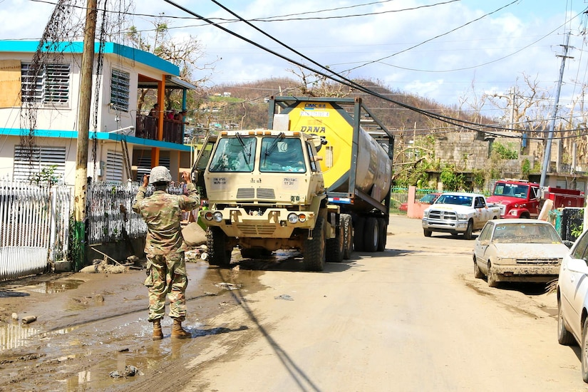 A Guardsman ground guides while directing a truck transporting a large amount of water to be distributed to residents in the San Jose community in Toa Baja.