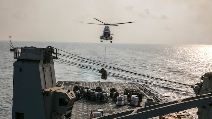 (170923-M-DJ953-0142) U.S. 5th FLEET AREA OF OPERATIONS (Sept. 24, 2017) – A helicopter descends to deliver cargo aboard USS Pearl Harbor (LSD 52) during a vertical replenishment (VERTREP) with the Lewis and Clark-class dry cargo ship USNS Washington Chambers (T-AKE 11).  The 15th Marine Expeditionary Unit is embarked on the America Amphibious Ready Group and is deployed to maintain regional security in the U.S. 5th Fleet area of operations. (U.S. Marine Corps photo by Cpl. F. Cordoba)