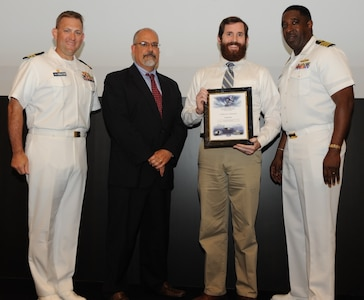 IMAGE: DAHLGREN, Va. - Stephen Dix receives his certificate of achievement from Naval Surface Warfare Center Dahlgren Division (NSWCDD) Technical Director John Fiore, NSWCDD Commanding Officer Capt. Godfrey 'Gus' Weekes, right, and Combat Direction Systems Activity Dam Neck Commanding Officer Cmdr. Andrew Hoffman at the 2017 NSWCDD academic awards ceremony. Dix was recognized for completing his master's in mechanical engineering from Old Dominion University, and commended for his commitment to personal and professional development.