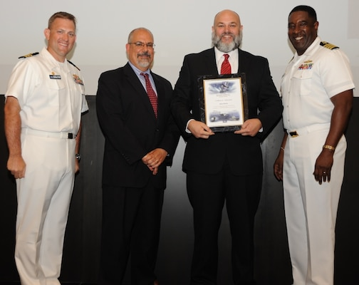 IMAGE: DAHLGREN, Va. - Shawn Richey receives his certificate of achievement from Naval Surface Warfare Center Dahlgren Division (NSWCDD) Technical Director John Fiore, NSWCDD Commanding Officer Capt. Godfrey 'Gus' Weekes, right, and Combat Direction Systems Activity Dam Neck Commanding Officer Cmdr. Andrew Hoffman at the 2017 NSWCDD academic awards ceremony. Finnie was recognized for completing his master's in information systems from Strayer University, and commended for his commitment to personal and professional development.