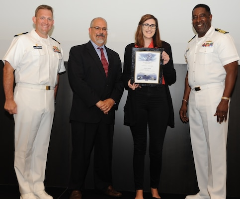 IMAGE: DAHLGREN, Va. - Kimberly Howell receives her certificate of achievement from Naval Surface Warfare Center Dahlgren Division (NSWCDD) Technical Director John Fiore, NSWCDD Commanding Officer Capt. Godfrey 'Gus' Weekes, right, and Combat Direction Systems Activity Dam Neck Commanding Officer Cmdr. Andrew Hoffman at the 2017 NSWCDD academic awards ceremony. Howell was recognized for completing her bachelor's in mathematics from Virginia Tech, and commended for her commitment to personal and professional development.