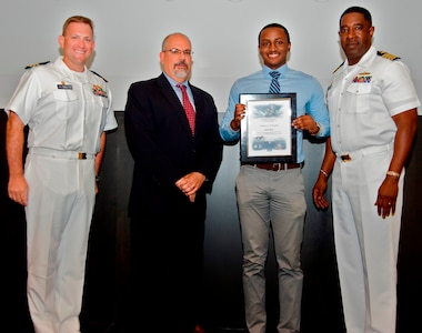 IMAGE: DAHLGREN, Va. - James Finnie receives his certificate of achievement from Naval Surface Warfare Center Dahlgren Division (NSWCDD) Technical Director John Fiore, NSWCDD Commanding Officer Capt. Godfrey 'Gus' Weekes, right, and Combat Direction Systems Activity Dam Neck Commanding Officer Cmdr. Andrew Hoffman at the 2017 NSWCDD academic awards ceremony. Finnie was recognized for completing his master's in cybersecurity engineering from Morgan State University, and commended for his commitment to personal and professional development.