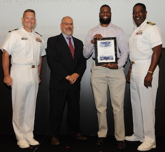 IMAGE: DAHLGREN, Va. - Brent Reid receives his certificate of achievement from Naval Surface Warfare Center Dahlgren Division (NSWCDD) Technical Director John Fiore, NSWCDD Commanding Officer Capt. Godfrey 'Gus' Weekes, right, and Combat Direction Systems Activity Dam Neck Commanding Officer Cmdr. Andrew Hoffman at the 2017 NSWCDD academic awards ceremony. Pasanen was recognized for completing his master's in cybersecurity engineering from Morgan State University, and commended for his commitment to personal and professional development.
