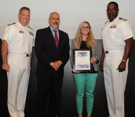 IMAGE: DAHLGREN, Va. - Lauren Pasanen receives her certificate of achievement from Naval Surface Warfare Center Dahlgren Division (NSWCDD) Technical Director John Fiore, NSWCDD Commanding Officer Capt. Godfrey 'Gus' Weekes, right, and Combat Direction Systems Activity Dam Neck Commanding Officer Cmdr. Andrew Hoffman at the 2017 NSWCDD academic awards ceremony. Pasanen was recognized for completing her bachelor's in electrical engineering from Old Dominion University, and commended for her commitment to personal and professional development.