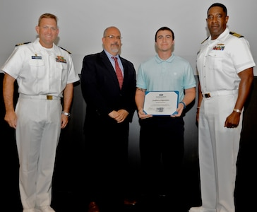 IMAGE: DAHLGREN, Va. - David Frederickson receives his certificate of achievement from Naval Surface Warfare Center Dahlgren Division (NSWCDD) Technical Director John Fiore, NSWCDD Commanding Officer Capt. Godfrey 'Gus' Weekes, right, and Combat Direction Systems Activity Dam Neck Commanding Officer Cmdr. Andrew Hoffman at the 2017 NSWCDD academic awards ceremony. Frederickson was recognized for completing his master's in business administration from Old Dominion University, and commended for his commitment to personal and professional development.