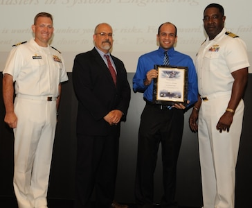 IMAGE: DAHLGREN, Va. - Jose Martinez-Casiano receives his certificate of achievement from Naval Surface Warfare Center Dahlgren Division (NSWCDD) Technical Director John Fiore, NSWCDD Commanding Officer Capt. Godfrey 'Gus' Weekes, right, and Combat Direction Systems Activity Dam Neck Commanding Officer Cmdr. Andrew Hoffman at the 2017 NSWCDD academic awards ceremony. Martinez-Casiano was recognized for completing his master's in systems engineering from the Naval Postgraduate School, and commended for his commitment to personal and professional development.