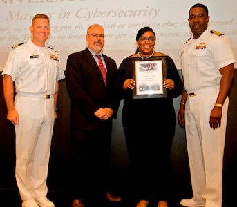 IMAGE: DAHLGREN, Va. - Quinnesha Staton receives her certificate of achievement from Naval Surface Warfare Center Dahlgren Division (NSWCDD) Technical Director John Fiore, NSWCDD Commanding Officer Capt. Godfrey 'Gus' Weekes, right, and Combat Direction Systems Activity Dam Neck Commanding Officer Cmdr. Andrew Hoffman at the 2017 NSWCDD academic awards ceremony. Staton was recognized for completing her master's in cybersecurity from the University of Maryland University College, and commended for her commitment to personal and professional development.