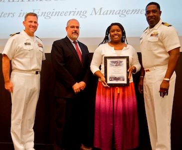 IMAGE: DAHLGREN, Va. - Tanika Hooker receives her certificate of achievement from Naval Surface Warfare Center Dahlgren Division (NSWCDD) Technical Director John Fiore, NSWCDD Commanding Officer Capt. Godfrey 'Gus' Weekes, right, and Combat Direction Systems Activity Dam Neck Commanding Officer Cmdr. Andrew Hoffman at the 2017 NSWCDD academic awards ceremony. Hooker was recognized for completing her master's in engineering management from the University of Maryland University College, and commended for her commitment to personal and professional development.
