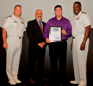 IMAGE: DAHLGREN, Va. - Cameron Sorlie receives his certificate of achievement from Naval Surface Warfare Center Dahlgren Division (NSWCDD) Technical Director John Fiore, NSWCDD Commanding Officer Capt. Godfrey 'Gus' Weekes, right, and Combat Direction Systems Activity Dam Neck Commanding Officer Cmdr. Andrew Hoffman at the 2017 NSWCDD academic awards ceremony. Sorlie was recognized for completing his master's in electrical engineering from John Hopkins University, and commended for his commitment to personal and professional development.