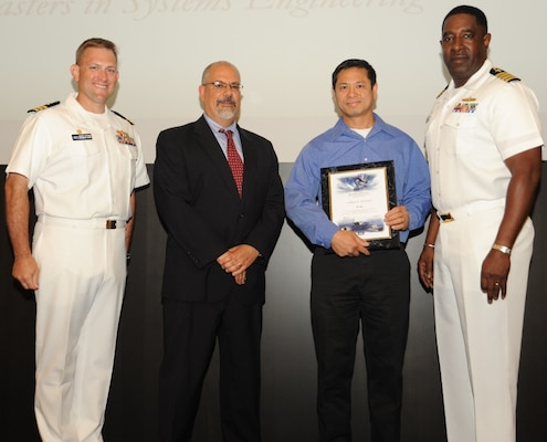 IMAGE: DAHLGREN, Va. - Tu Ngo receives his certificate of achievement from Naval Surface Warfare Center Dahlgren Division (NSWCDD) Technical Director John Fiore, NSWCDD Commanding Officer Capt. Godfrey 'Gus' Weekes, right, and Combat Direction Systems Activity Dam Neck Commanding Officer Cmdr. Andrew Hoffman at the 2017 NSWCDD academic awards ceremony. Ngo was recognized for completing his master's in systems engineering from the Naval Postgraduate School, and commended for his commitment to personal and professional development.