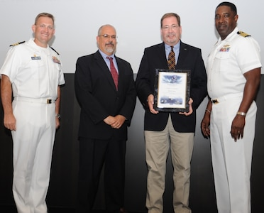 IMAGE: DAHLGREN, Va. - Richard Rowe receives his certificate of achievement from Naval Surface Warfare Center Dahlgren Division (NSWCDD) Technical Director John Fiore, NSWCDD Commanding Officer Capt. Godfrey 'Gus' Weekes, right, and Combat Direction Systems Activity Dam Neck Commanding Officer Cmdr. Andrew Hoffman at the 2017 NSWCDD academic awards ceremony. Rowe was recognized for completing his master's in national security and strategic studies from the Naval  War College, and commended for his commitment to personal and professional development.