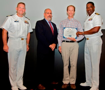 IMAGE: DAHLGREN, Va. - Joel Harrison receives his certificate of achievement from Naval Surface Warfare Center Dahlgren Division (NSWCDD) Technical Director John Fiore, NSWCDD Commanding Officer Capt. Godfrey 'Gus' Weekes, right, and Combat Direction Systems Activity Dam Neck Commanding Officer Cmdr. Andrew Hoffman at the 2017 NSWCDD academic awards ceremony. Harrison was recognized for completing his doctoral degree in electrical engineering from the University of Virginia, and commended for his commitment to personal and professional development.