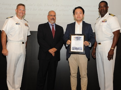 IMAGE: DAHLGREN, Va. - David Ferlemann receives his certificate of achievement from Naval Surface Warfare Center Dahlgren Division (NSWCDD) Technical Director John Fiore, NSWCDD Commanding Officer Capt. Godfrey 'Gus' Weekes, right, and Combat Direction Systems Activity Dam Neck Commanding Officer Cmdr. Andrew Hoffman at the 2017 NSWCDD academic awards ceremony. Ferlemann was recognized for completing his doctoral degree in computer engineering from the University of Tulsa, and commended for his commitment to personal and professional development.