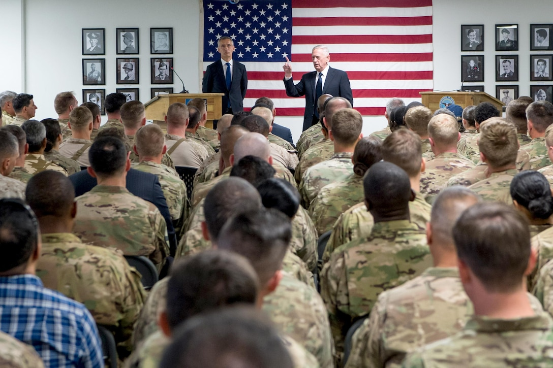 Defense Secretary Jim Mattis and the NATO secretary general talk to seated service members.