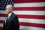 Defense Secretary Jim Mattis stands in front of an American flag.