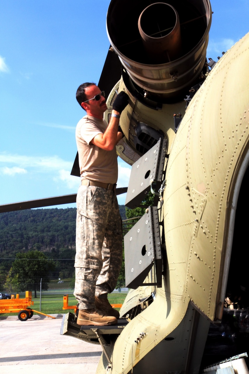 Army Chief Warrant Officer 4 Eric Ridilla, a maintenance test pilot with Company B, 628th Aviation Support Battalion, Pennsylvania National Guard, performs final checks on a CH-47 Chinook helicopter