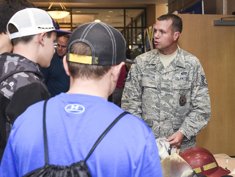 U.S. Air Force Tech Sgt. Jayton Washington, 312th Training Squadron instructor, explains how the various layers of their fire jackets protect firefighters from extreme heat during the Annual Business Expo in San Angelo, Texas, at the McNease Convention Center, Sept. 27, 2017. Washington described how the jacket weighs 22lbs and their combined gear weighs 110lbs. (U.S. Air Force photo by Aryn Lockhart/Released)