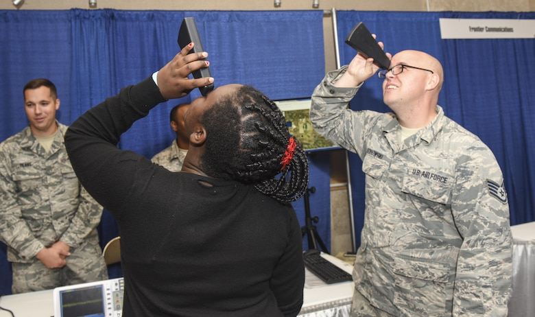 U.S. Air Force Tech Sgt. Robert Kedrowski, 312th Training Squadron course development specialist, demonstrates to a Glenn Middle School student how a spectroscope analyzes light during the Career Connection Symposium that took place during the San Angelo Texas Business Expo, at the McNease Convention Center, Sept. 27, 2017. The Career Connection Symposium allowed local eighth grade students to visit with exhibitors learning about career paths available in the Concho Valley. (U.S. Air Force photo by Aryn Lockhart/Released)