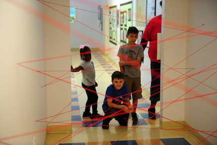 "Kyra Brown, left, Alex Rowell, center, and Julius Ruiz, right, wait their turn to try to navigate a ""laser maze"" while participating in Day for Kids at the Joint Base Charleston Weapons Station Youth Center Sept. 21, 2017."