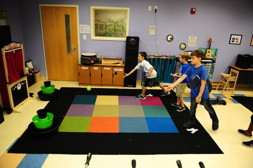 Alex Rowell, Near, Lucas Jessen, Middle, and Trenten Bunch, far, play bean bag toss during Day for Kids at the Joint Base Charleston Weapons Station Youth Center Sept. 21, 2017.