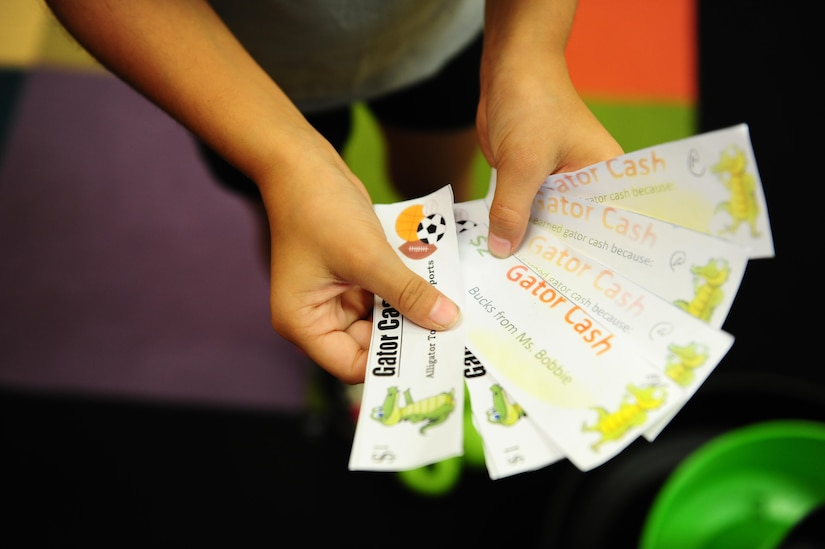 Briana Miller shows off the gator cash she earned for participating in Day for Kids at the Joint Base Charleston Weapons Station Youth Center Sept. 21, 2017