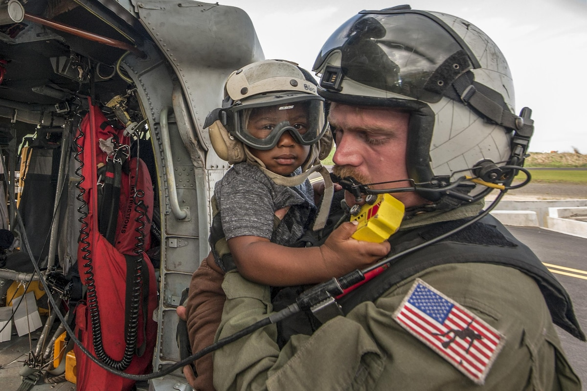 A sailor holds a child after a helicopter transported them.