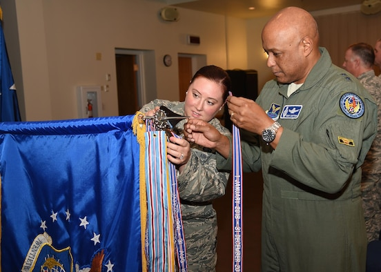 Gen Cotton and SSgt Bailey affix AFOUA ribbon for 2016 to 20AF guidon