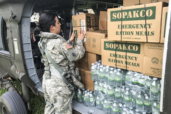 A soldier handles a cardboard box of emergency rations on a helicopter filled with provisions.