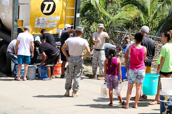 Guardsmen distribute water to residents in the San Jose community in Toa Baja.