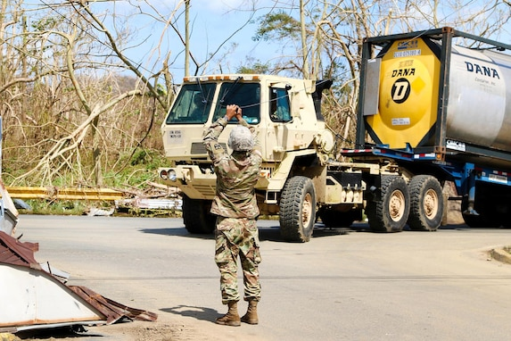 A Guardsman clears a power line for a truck transporting a large amount of water to be distributed to residents in the San Jose community in Toa Baja.