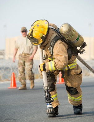 U.S. Air Force Senior Airman John Hodgkins, firefighter with the 379th Expeditionary Civil Engineer Squadron's Fire and Emergency Services Flight, drags a hose 150 feet to the end of station two during a firefighter combat challenge at Al Udeid Air Base, Qatar, Sept. 1, 2017.