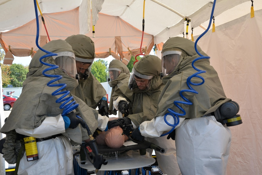 Members of the In-Place Patient Decontamination Team clean a mock patient at a wash station during IPPD training Sept. 28 at the base clinic.