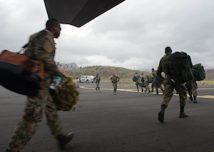 Jamaican Defense Force disaster response team soldiers exit the back of an aircraft in Dominica,