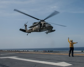 A Sailor signals the take off of a U.S. Army helicopter from the flight deck of the amphibious assault ship USS Wasp