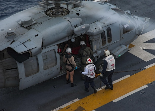 Sailors escort a rescued resident of French Guadalupe from a helicopter on the flight deck of USS Wasp.