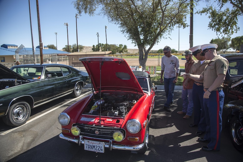 A local member of the community takes time to discuss features of his car with Marines from the Provost Marshal's Office during the first car show at Lucky Park, Twentynine Palms, Calif., September 23, 2017. Marines from motor transportation, military police and explosive ordnance disposal came out to help the continuing effort to foster a positive relationship with the community by showing what resources the military has to offer. (Marine Corps photo by Pfc. Margaret Gale)