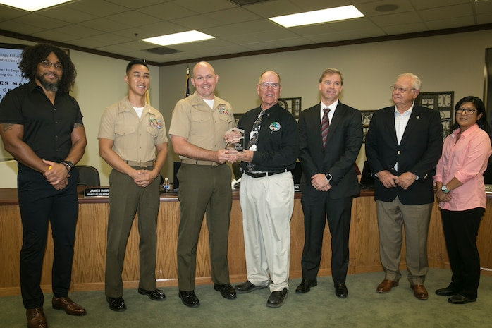 Col. Jay Wylie, assistant chief of staff, G-4 Installation and Logistics, and Maj. David Tran, environmental engineering management officer, G-4 Installation and Logistics, accept the Exemplar Award on behalf of the Marine Corps Air Ground Combat Center at the Mojave Desert Air Quality Management District headquarters, September 25, 2017. MDAQMD awarded the Combat Center for its dedication to utilizing clean energy and reducing emissions of greenhouse gasses.(U.S. Marine Corps photo by Lance Cpl. Isaac Cantrell)