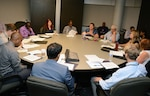 PaCE program participants sit at conference table during in-processing