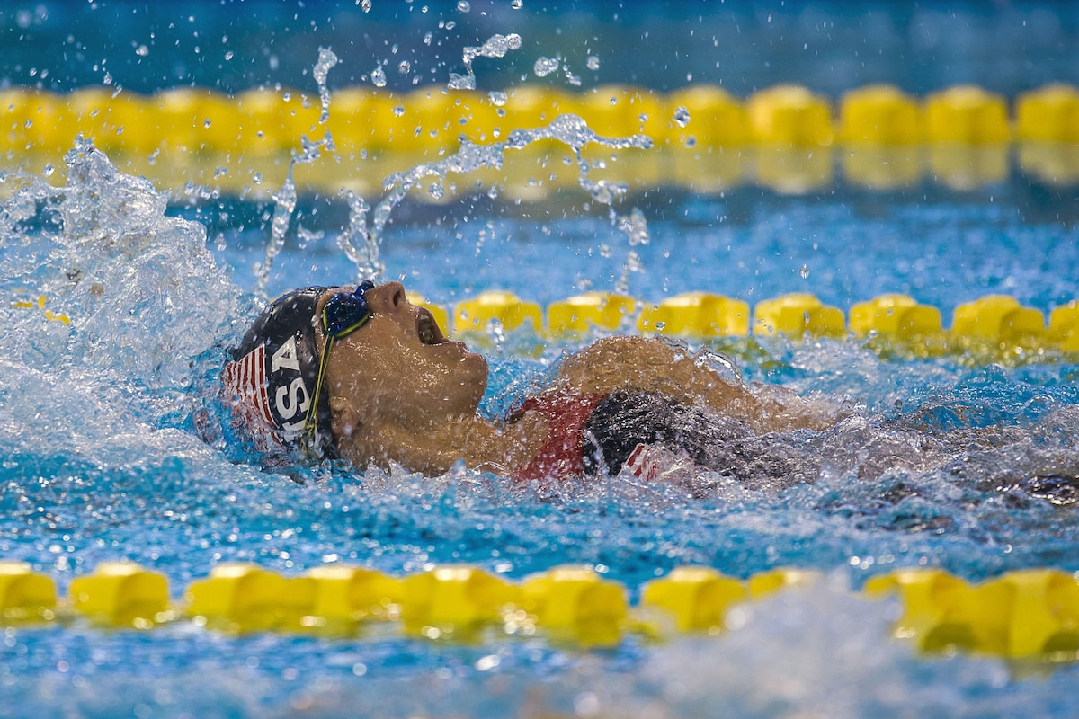An athlete swims backstroke.