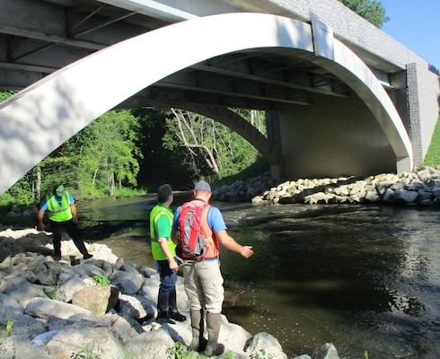 USACE regulator, Douglas Kapusinski, discusses permit compliance with representatives from the Summit County Engineers office, at a bridge replacement project site.