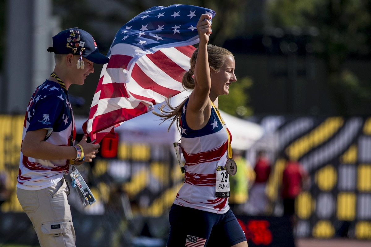 A Marine veteran runs with a smile on her face, holding an American flag.
