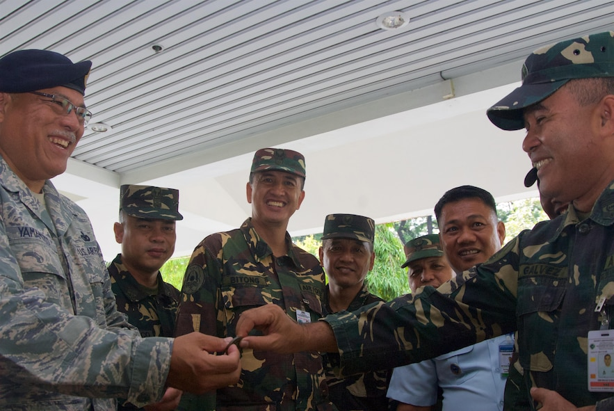 Chief Master Sgt. Melvin Yamamoto, superintendent, 154th Security Forces, coins Philippine Air Force Master Sgt. Manuel Galvez