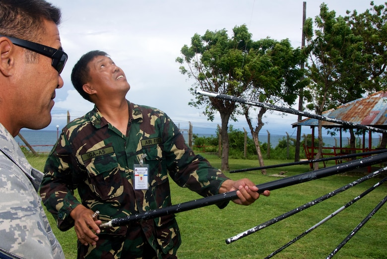 Master Sgt. Morris Niibu, an RF Transmissions System Technician with the 169th Air Defense Squadron, observes a member of the Philippine Air Force preparing to install a radio communications antenna