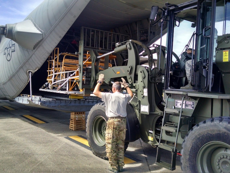 A 302nd Airlift Wing loadmaster guides a cargo load onto an Air Force Reserve Command C-130 Hercules aircraft Sept. 25, at the San Juan International Airport, Puerto Rico.