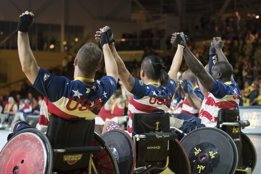 Left to right: Air Force veteran Master Sgt. Jesse Graham, Air Force veteran Staff Sgt. Sebastiana Lopez-Arellano and Army veteran Army Cpt. William Reynolds join hands with the rest of the U.S. wheelchair rugby team after receiving bronze medals during the 2017 Invictus Games at the Mattamy Athletic Centre in Toronto, Sept. 28, 2017. The Invictus Games, established by Prince Harry in 2014, brings together wounded and injured veterans from 17 nations for 12 adaptive sporting events, including track and field, wheelchair basketball, wheelchair rugby, swimming, sitting volleyball, and new to the 2017 games, golf. DoD photo by Roger L. Wollenbe
