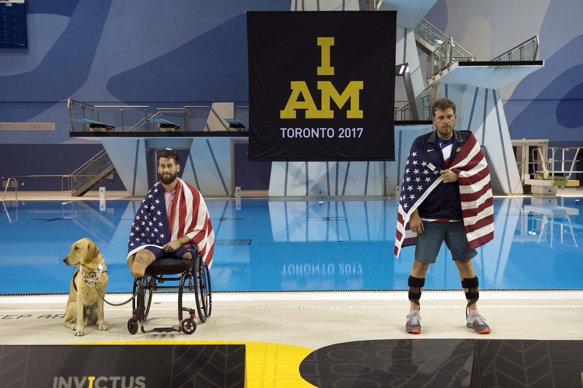 Two wounded warriors draped in the american flag take the stage, one in a wheelchair while holding the leash to a dog,