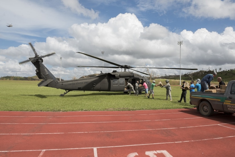 In San Juan, Puerto Rico National Guardsmen load pallets of food and water onto an UH-60 Black Hawk helicopter for distribution to Orocovis, Puerto Rico, Sept. 29, 2017. The National Guard has partnered with the Federal Emergency Management Agency and other state and federal agencies in response and relief operations for Hurricane Maria. Air National Guard photo by Air Force Staff Sgt. Michelle Y. Alvarez-Rea
