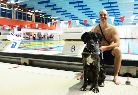 U.S. Coast Guard Petty Officer 1st Class Rob Troha, an intelligence specialist and member of Team U.S. at the 2017 Invictus Games poses with his service dog Gauge, moments after his swimming event at the Pan Am Sports Centre Toronto, Canada Sept. 28, 2017. Troha, who suffers from a degenerative brain disorder, also competed in seated discus and shotput in this year's games. (U.S. Air Force photo by Staff Sgt. Chip Pons)