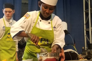 A Navy chef mixes ingredients for a meal in a bowl during a culinary competition.